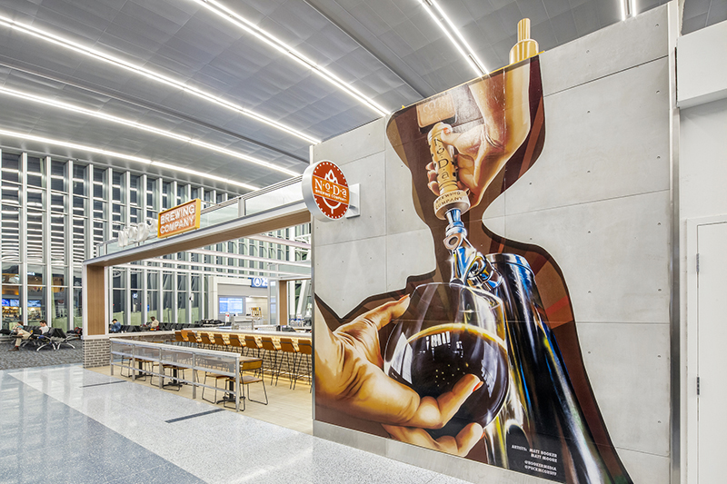 A mural designed by Matt Hooker and Matt Moore appears at NoDa Brewing Company's airport location.