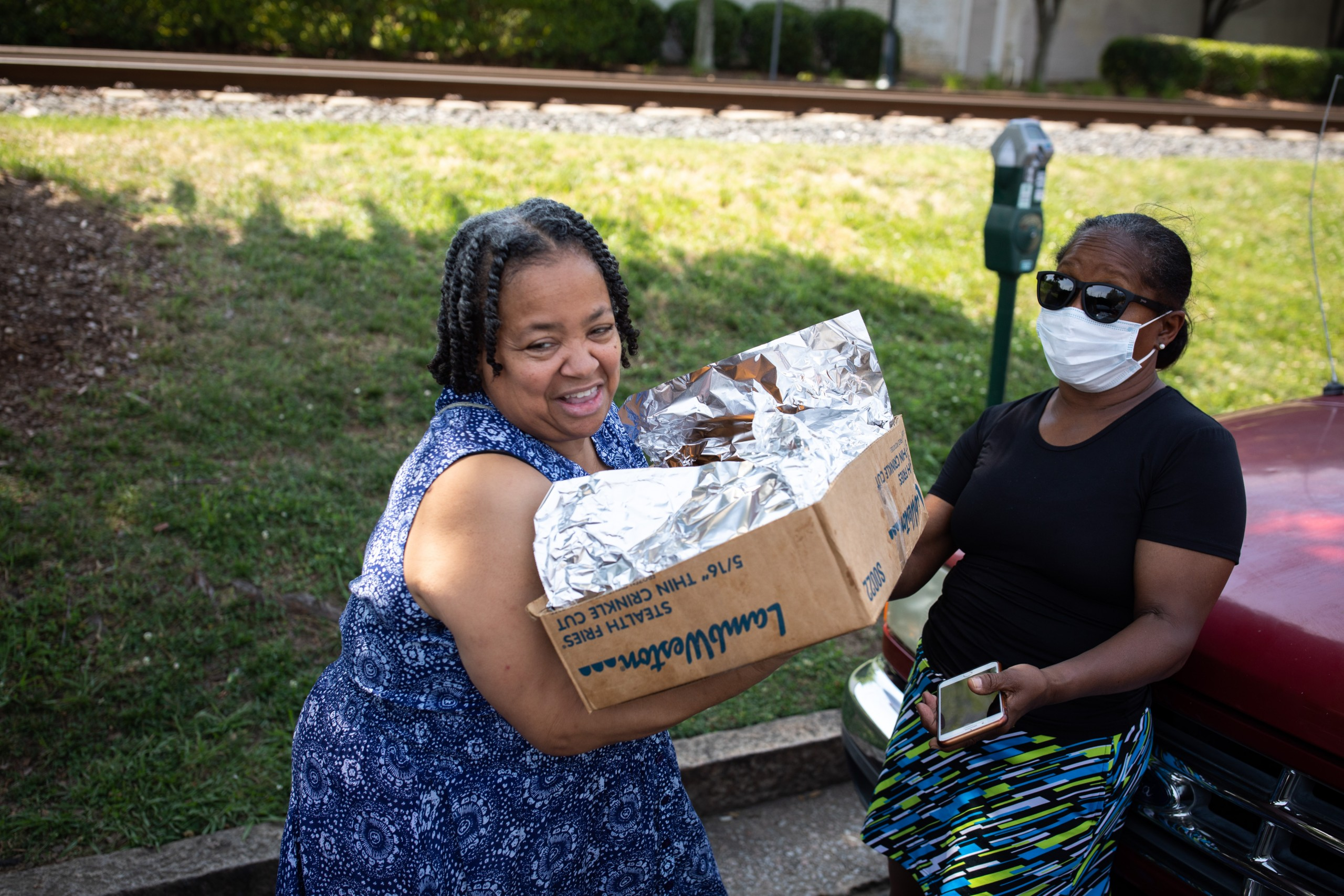 Von Holloman Carries A Box Of 100 Wings To The Trunk Of Her Car.